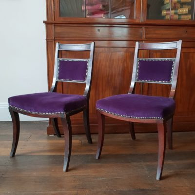 Pair of Regency saddle seat sabre leg chairs c 1810.