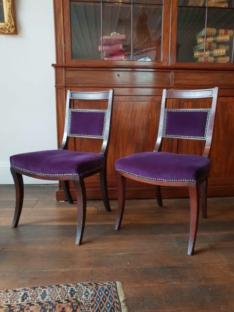 Pair of Regency saddle seat sabre leg chairs c 1810.